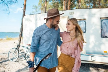 young hippie couple hugging and walking near trailer