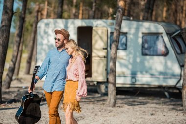 hippie couple in sunglasses hugging and walking with acoustic guitar near trailer in forest