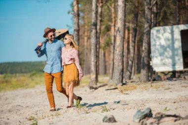 beautiful young couple hugging and walking with acoustic guitar in forest