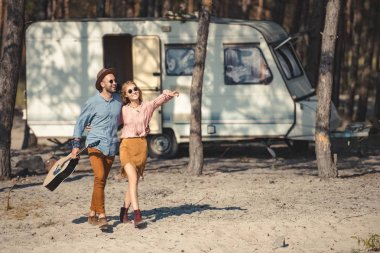 young couple in sunglasses hugging and walking with acoustic guitar near trailer in forest, girl showing something