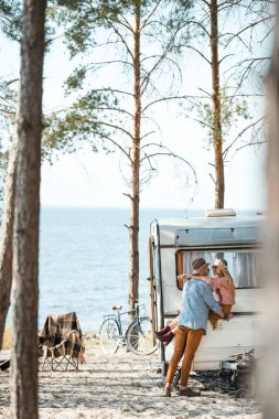 hippie couple embracing and sitting on campervan in forest near sea
