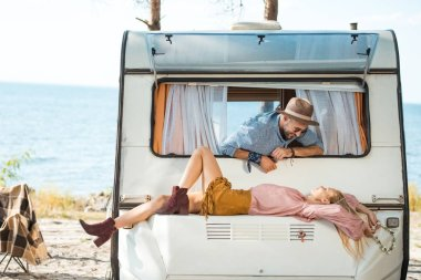 beautiful hippie couple relaxing on campervan near the sea