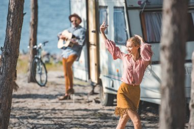 young hippie woman dancing while man playing guitar near trailer