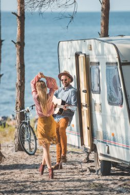 hippie couple dancing and playing guitar near trailer in nature
