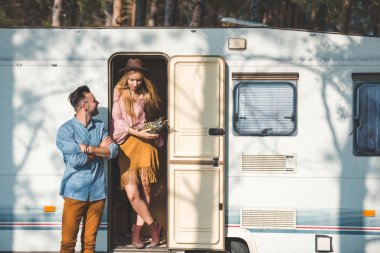 young hippie couple with pineapple posing near trailer in camp
