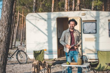smiling man cutting avocado near campervan in forest