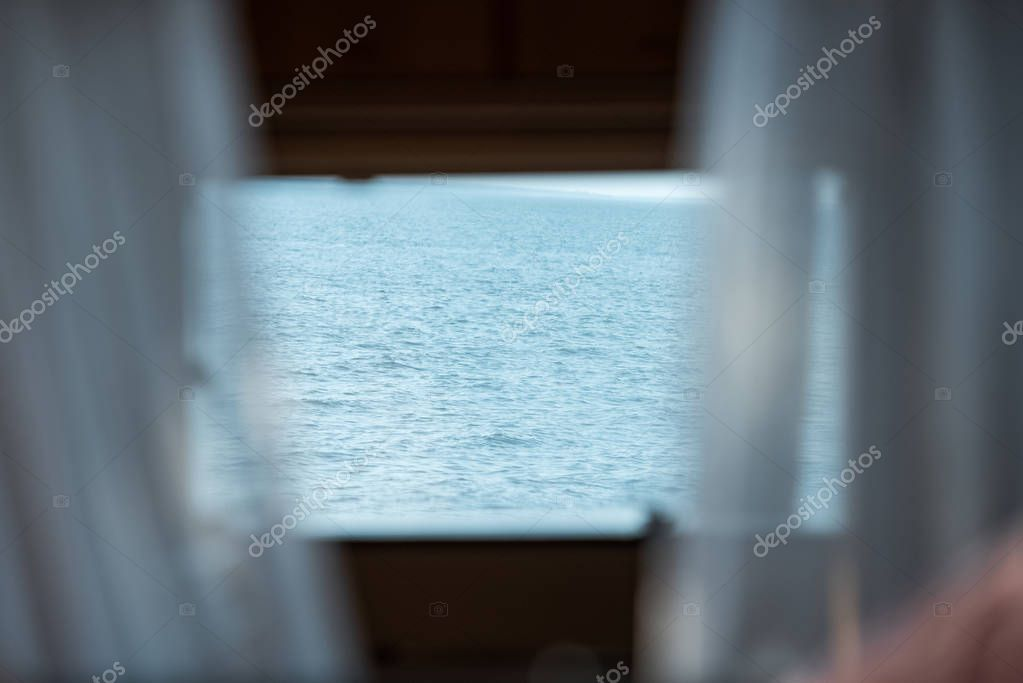 view of blue sea from trailer window with curtains