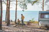 Photo hippie couple having picnic with guitar at trailer near the sea