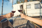 Fotografie cropped view of couple clinking with glasses of wine during picnic in camp