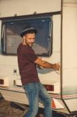 pohledný muž snaží otevřít dveře campervan
