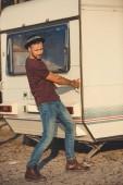 pohledný muž v klobouku snaží otevřít dveře campervan
