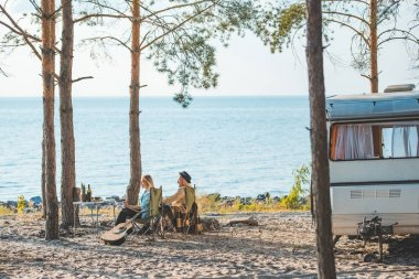 young couple having picnic at campervan near the sea