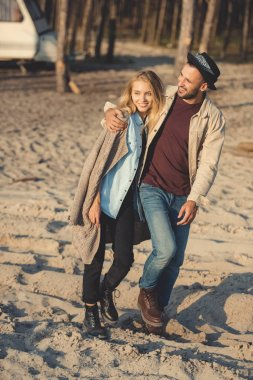 smiling man and attractive woman hugging and walking on sand beach