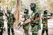paintball team in uniform and protective masks playing paintball with marker guns outdoors