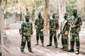paintball team in uniform and goggle masks standing with paintball guns outdoors