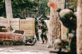selective focus of paintball player doing follow me gesture to his paintball team in camouflage and masks outdoors