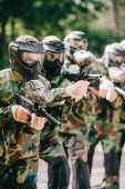 focused female paintball player holding marker gun with her team in protective masks and camouflage playing paintball outdoors
