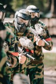 paintball players in goggle masks and camouflage uniform holding paintball guns outdoors