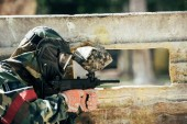 rear view of paintball player in goggle mask and camouflage aiming by paintball gun outdoors