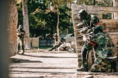 paintball players in camouflage and protective masks aiming with marker guns and hiding behind wooden wall outdoors
