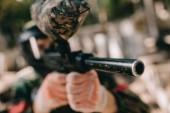Selektivní fokus paintballové hráče v maskování zaměřené paintball Gun venku