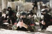 Selektivní fokus koncentrované paintballové hráče ochranná maska míření s pistolí značky a jeho tým na pozadí venku