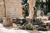 selective focus of paintball player laying on ground and aiming with marker gun and his team hiding behind wooden wall outdoors