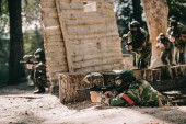 Fényképek paintball player laying on ground and aiming by marker gun while his team hiding behind wooden wall outdoors