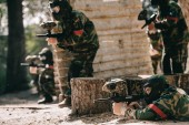 Fényképek focused paintball player laying on ground and aiming with marker gun while his team hiding behind wooden wall outdoors