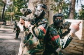 male paintball player in camouflage and goggle mask pointing by finger to his teammate with marker gun standing near tree outdoors