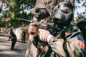 Paintball hráčů v maskování a ochranné masky mluví a schovává se za strom venku