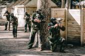Paintball hráči na sobě zamaskovat a brýle masky Střelba zbraně značky u stromu a jejich tým na pozadí venku