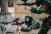 Selektivní fokus paintballové hráče brýle maska míření zbraní značky poblíž spoluhráč venku