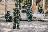 paintball team in camouflage uniform with marker guns resting near broken car outdoors
