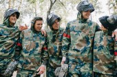 smiling paintball players in camouflage with marker guns talking and embracing each other outdoors