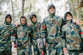 happy paintball players in camouflage with marker guns embracing each other outdoors