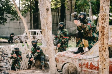 paintball team in uniform and protective masks playing paintball with marker guns on broken car outdoors