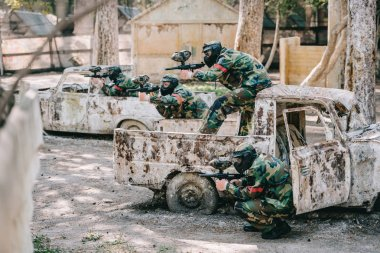 paintball team in camouflage and goggle masks aiming with marker guns from broken cars outdoors