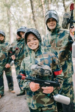 beautiful happy female paintballer in uniform holding paintball gun while her team standing behind outdoors