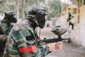 side view of male paintballer and his team in uniform and protective masks aiming by paintball guns outdoors
