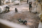high angle view of paintball team in uniform and protective masks playing paintball with markers guns outdoors