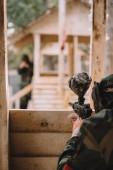 částečný pohled paintballové hráče v maskování jednotným cílem paintball Gun z dřevěné věže venku