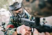 Selektivní fokus hráče mužského paintball brýle masky a maskování zaměřené paintball zbraň venku