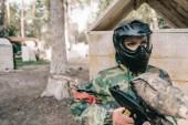 Fényképek a védő maszkot és álcázás egységes álló paintball fegyvert szabadban súlyos női paintballer