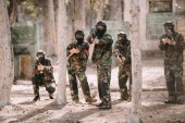 paintball team in uniform and protective masks aiming by paintball guns outdoors