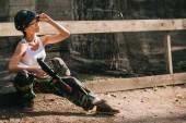 Fényképek fiatal női paintballer, a fehér szingulett goggle maszk felhelyezése és a gazdaság paintball fegyver szabadban