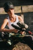 Fényképek szép fiatal női paintballer fehér szingulett és bámészkodik maszk kint tartja a paintball fegyver