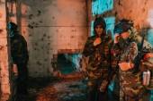 mladý muž paintballové hráče v jednotné a ochranné masky odpočívá v opuštěné budově