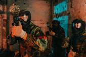 paintball team in uniform and protective masks playing paintball with marker guns in abandoned building