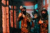 paintball tým v jednotné a ochranné masky zaměřené paintball zbraně v opuštěné budově